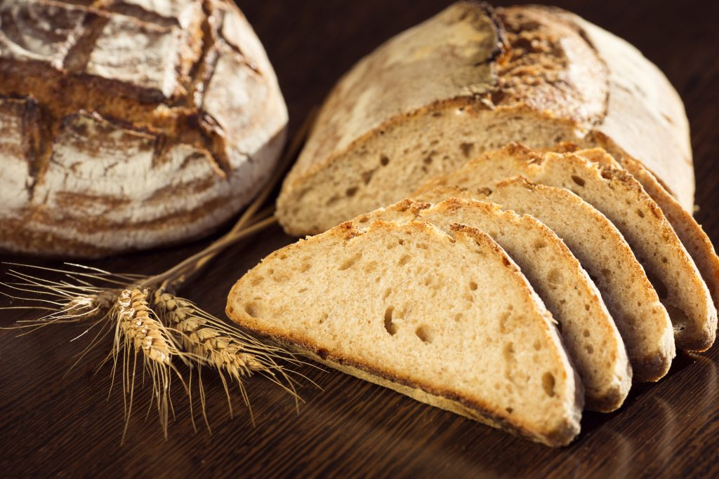 Rustic bread and wheat on a dark brown fundal